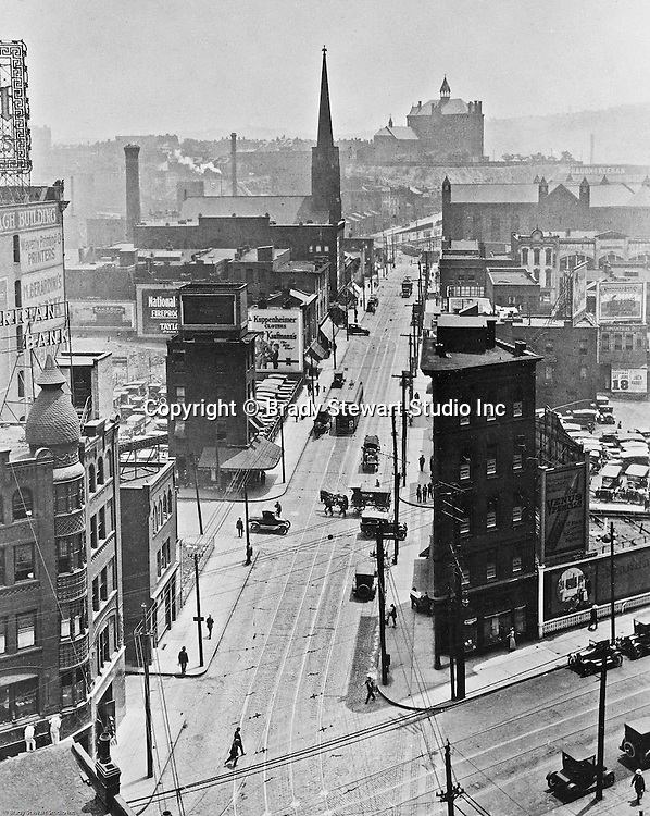 Pittsburgh PA: View of Duquesne University from the corner of Grant Street and Sixth Avenue - 1920.  During this time, it was common for Brady Stewart to get on a roof of an office building and take photographs.  Company signs on city buildings include:  Venus Pencils, American Bank, M. Berardini's Bank, National Fireproof Company,  Waverly Printing Company, and Kuppenheimer Clothes at Kaufmann's Store