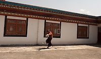 A moment in the day of a Buddhist student-monk at a monastery in the Himalayan foothills of Sikkim, India. Playing soccer in the afternoon break in his robes.