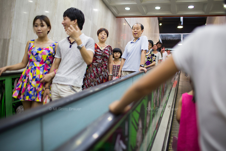 People ride a moving walkway in a grocery store in Xian, Shaanxi, China.