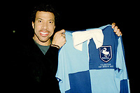 American singer songwriter, composer, Lionel Richie holds up a Wycombe Wanderers shirt ahead of kick-off as he walked around the ground meeting fans during Wycombe Wanderers vs Notts County, Nationwide League Division Two Football at Adams Park on 6th October 2000