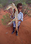 The goanna has an important place in Australian aboriginal culture.  Not only is it a food source, but its spirit is a protector and associated with rain.  A boy proudly holds his catch.
