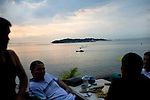 Indonesians relax over coffee and snacks at Hotel Sadaap, in Tanjung Pinang, Bintan, with views of island of Penyengat, Indonesia, on Monday, April 19, 2010.