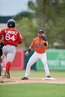 Baltimore Orioles J.C. Escarra (72) waits to receive a throw as Gilberto Jimenez (64) runs up the first base line during a Florida Instructional League game against the Boston Red Sox on October 8, 2018 at the Ed Smith Stadium in Sarasota, Florida.  (Mike Janes/Four Seam Images)
