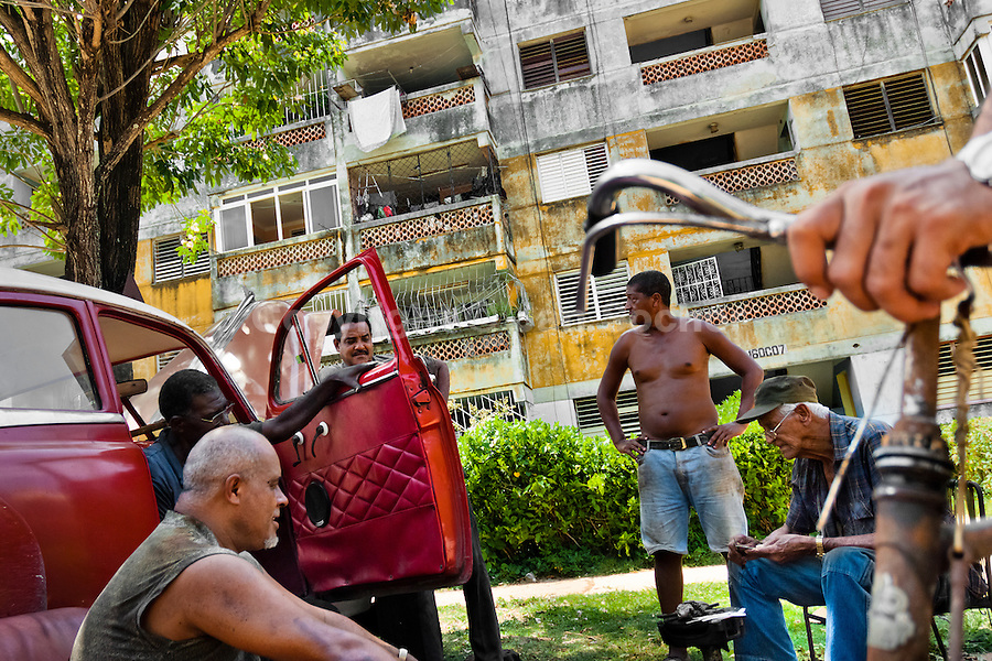 """Cuban men repair an American classic car from 1950s in front of the apartment block in Alamar, a public housing complex in the Eastern Havana, Cuba, 14 August 2008. The Cuban economic transformation (after the revolution in 1959) has changed the housing status in Cuba from a consumer commodity into a social right. In 1970s, to overcome the serious housing shortage, the Cuban state took over the Soviet Union concept of social housing. Using prefabricated panel factories, donated to Cuba by Soviets, huge public housing complexes have risen in the outskirts of Cuban towns. Although these mass housing settlements provided habitation to many families, they often lack infrastructure, culture, shops, services and well-maintained public spaces. Many local residents have no feeling of belonging and inspite of living on a tropical island, they claim to be """"living in Siberia""""."""