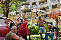 "Cuban men repair an American classic car from 1950s in front of the apartment block in Alamar, a public housing complex in the Eastern Havana, Cuba, 14 August 2008. The Cuban economic transformation (after the revolution in 1959) has changed the housing status in Cuba from a consumer commodity into a social right. In 1970s, to overcome the serious housing shortage, the Cuban state took over the Soviet Union concept of social housing. Using prefabricated panel factories, donated to Cuba by Soviets, huge public housing complexes have risen in the outskirts of Cuban towns. Although these mass housing settlements provided habitation to many families, they often lack infrastructure, culture, shops, services and well-maintained public spaces. Many local residents have no feeling of belonging and inspite of living on a tropical island, they claim to be ""living in Siberia""."