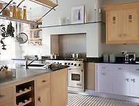 A modern kitchen with pale blue and wood units. A stainless steel range oven is set in a recess and a sink unit is built in to the worktop of a central island unit.