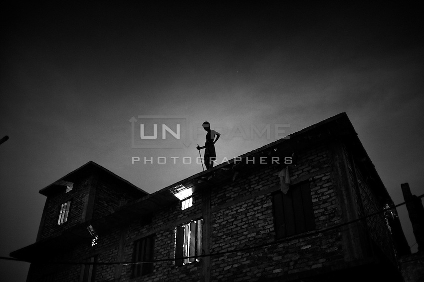 A man stands on the roof of a factory in the Hazaribag Area, Dhaka, Bangladesh