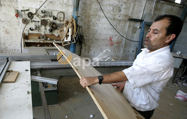 A Palestinian carpenter working in a wood workshop in Rafah the southern Gaza Strip on July 18, 2009. Palestinian merchants are dependent on goods smuggled through tunnels under the land between Egypt and Gaza due to the closure of the crossings of the Gaza Strip and Israel does not allow the entry of construction materials, cement and wood and iron from the Gaza Strip crossings. Photo By Abed Rahim Khatib