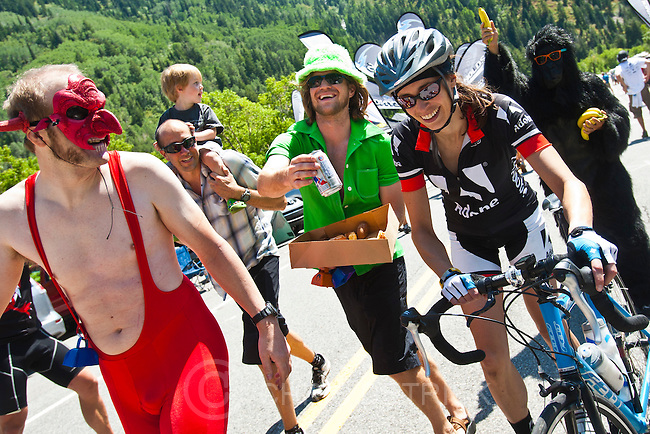 'Chris Detrick  |  The Salt Lake Tribune.Devil Wes Slaughter, leprechaun Mark Robinson, and gorilla Kevin Hashimoto offer beer, doughnuts and bananas to biker Julie Greenspoon as she races up Little Cottonwood Canyon during the Ultimate Challenge presented by Larry H. Miller Tour of Utah Saturday August 11, 2012. The traditional 100-mile route features 9,456 feet of climbing and a summit finish at Snowbird Ski and Summer Resort