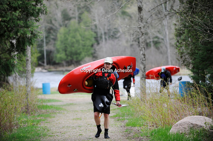 """A group of whitewater enthusiasts May 10, 2008 carry their kayaks along a trail that leads to the top of """"Gilmore's Mistake,"""" a rapids on the Wolf River, WI that becomes a Class III category during high water in the spring. The river is famous for its rafting, canoeing and kayaking opportunities, as well as for the outstanding trout and bass fishing."""