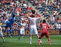 New York goalkeeper Bouna Coundoul (18) knocks away a cross intended for Chicago forward Diego Chaves (99), who is defended by New York defender Jan Gunnar Solli (8).  The Chicago Fire tied the New York Red Bulls 1-1 at Toyota Park in Bridgeview, IL on June 26, 2011.
