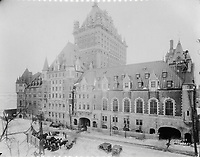 Front of the Chateau Frontenac with horses and sleds, photograph, 1923, from the Archives of the Chateau Frontenac, Quebec City, Quebec, Canada. The Chateau Frontenac opened in 1893 and was designed by Bruce Price as a chateau style hotel for the Canadian Pacific Railway company or CPR. It was extended in 1924 by William Sutherland Maxwell. The building is now a hotel, the Fairmont Le Chateau Frontenac, and is listed as a National Historic Site of Canada. The Historic District of Old Quebec is listed as a UNESCO World Heritage Site. Copyright Archives Chateau Frontenac / Manuel Cohen