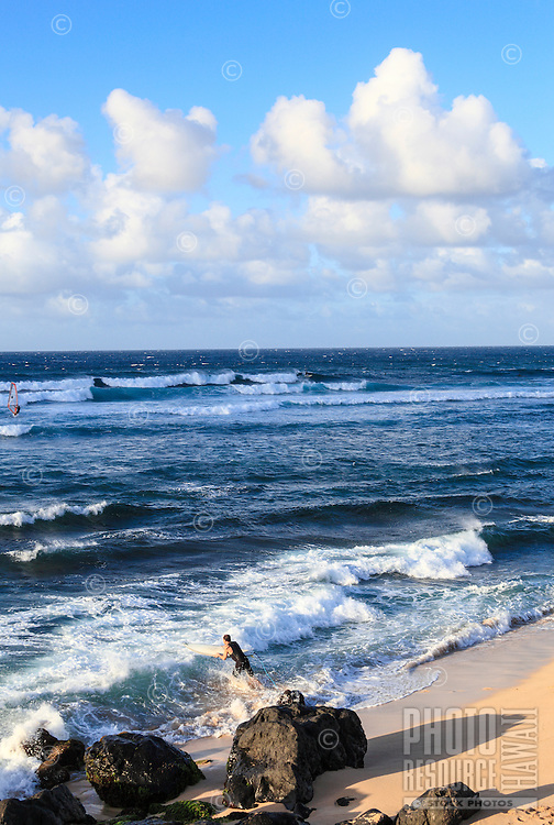 A surfer plunges into the ocean to join more distant surfers and a windsurfer at Ho'okipa Beach, Maui.