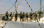 Israeli soldiers monitor a demonstration by Palestinian and foreign protestors against the construction of the controversial Israeli separation barrier in the West Bank village of Maasarah near Bethlehem.