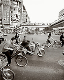 CHINA, Hangzhou, people riding bicycles and motorbike with bridge in the background (B&W)