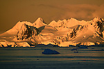 Morning light shines on the mountains of Antarctica, while the icebergs in the ocean remain shadowed.
