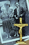 Free-standing small crucifix painted gold with figure of Jesus on it lying on black and white photo of family group in back garden