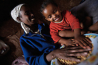 Emembet Albachew, 26 years old, HIV positive, cleans dry pies with her daughter Magdass in their home in a very poor neghborhoood in Addis Ababa, Ethiopia on Monday June 12 2006. Emembet lives with her daughter, 3 years old Magdass, her only reason to live. On June 20th she was reported to be dead by the St Paul hospital staff while she was enduring a deep physical crises. after almost 4 weeks of hospitalization she was discharged and could finally reunite with her daughter that meanwhile lived with a local home base care giver. . Ethiopia is one of the countries most affected by HIV/AIDS. Of its population of 77 million, three million are HIV-positive, according to government statistics. Every day sees 1,000 new infections. A million children under 14 have lost one or both parents to AIDS, and 200,000 children are living with AIDS. That makes Ethiopia the country with the most HIV-positive children.