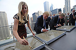 (L-r) Ivanka Trump, Donald Trump and Eric Trump write their names beside hand imprints at the topping-off ceremony of the new 92-story tall Trump International Hotel and Tower building in Chicago, Illinois on September 24, 2008.  The building will be the tallest in North America upon its completion in six months.