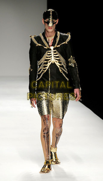 MODEL .At the MAN Show, Menswear Day, London Fashion Week - Day 6, Somerset House, London, England, UK, September 23rd 2009..full length modeling catwalk runway gold skeleton uniform jacket legs tattoo body paint bones military mask hat shorts shoes sandals armor .CAP/CAN.©Can Nguyen/Capital Pictures