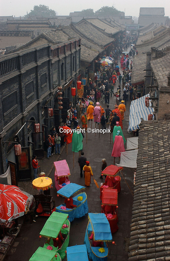 A traditional Chinese parade in Pingyao of Shannxi, which is one of the last cities in China that retains traditional Chinese architecture..19-SEP-04