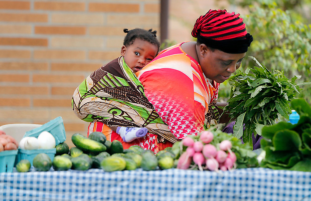 Burundian immigrant Beuline Bucumi assembles her produce as her granddaughter, Sadia, 1, rests in a sling on her back during the Global Greens Farmers Market at Lutheran Services in Iowa on Saturday, August 23, 2014 in Des Moines.  The market, launched in June, features fruits and vegetables grown by displaced farmers who have resettled in Iowa.