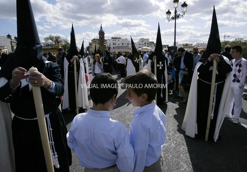 Two boys shat and  penitents take part in the El Cachorro  brotherhood procession during the Holy Week in Sevilla on April  , 2009.