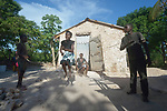 Erm Jouna Dalmas, 10, jumps rope in front of her family's new house on the Haitian island of La Gonave. Her siblings Vestander and Erm hold the rope as their mother looks on. Service Chr&eacute;tien d&rsquo;Ha&iuml;ti is working with survivors of Hurricane Matthew, which struck the region in 2016, to rebuild damaged housing. A member of the ACT Alliance, SCH also supports agriculture on the island by providing tools, seeds, and technical support and training for farmers.<br /> <br /> Parental consent obtained.