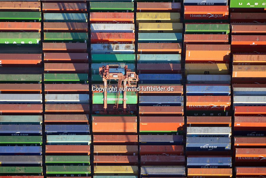 Portalhubwagen transportiert Container am Burchardkai: EUROPA, DEUTSCHLAND, HAMBURG, (EUROPE, GERMANY), 06.01.2016 Der Portalhubwagen (oder Portalhubstapelwagen oder Portalstapelwagen; engl. van carrier, straddle carrier, gantry lift ist ein spezielles Umschlaggeraet fuer ISO-Container. Es wird als Transportfahrzeug auf Containerterminals in Haefen eingesetzt.<br />  <br /> Der Portalhubwagen besteht aus einem Rahmengestell und einer dazwischen haengenden Hubvorrichtung Topspreader, das mit Hubwinden vertikal bewegt werden kann. Das Rahmengestell ist mit einem Fahrwerk mit meist acht Raedern ausgestattet. Die Fahrerkabine ist oben an einer Stirnseite des Rahmens angeflanscht.<br />  <br /> Der Portalhubwagen faehrt ueber einen Container, der auf dem Boden oder auf einem Lkw steht, der Spreader verriegelt sich hydraulisch gesteuert mit den vier Eckbeschlaegen des Containers und hebt diesen an.