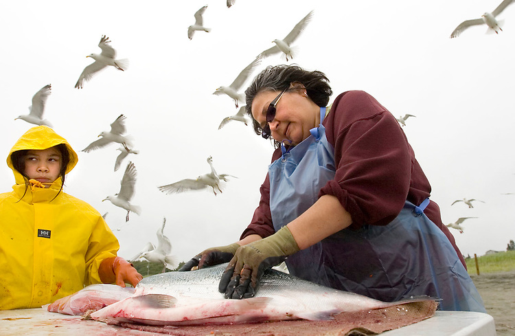 Bea Peterson, right,of Anchorage, Alaska, cleans a red salmon on the north bank of the Kenai River as her cousin Kiera Horst watches for family members to catch another fish.