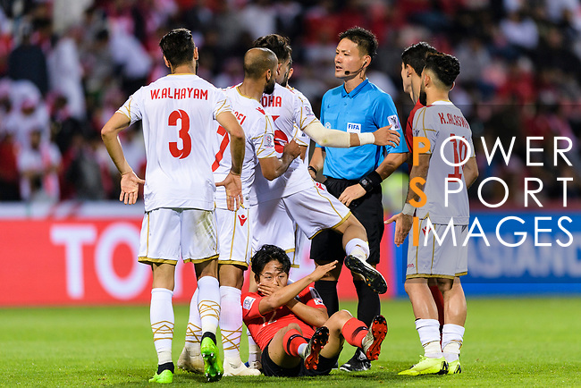 Players of Bahrain talk FIFA Referee Ryuji Sato of Japan while Lee Seungwoo of South Korea (bottom) lies injured during the AFC Asian Cup UAE 2019 Round of 16 match between South Korea (KOR) and Bahrain (BHR) at Rashid Stadium on 22 January 2019 in Dubai, United Arab Emirates. Photo by Marcio Rodrigo Machado / Power Sport Images