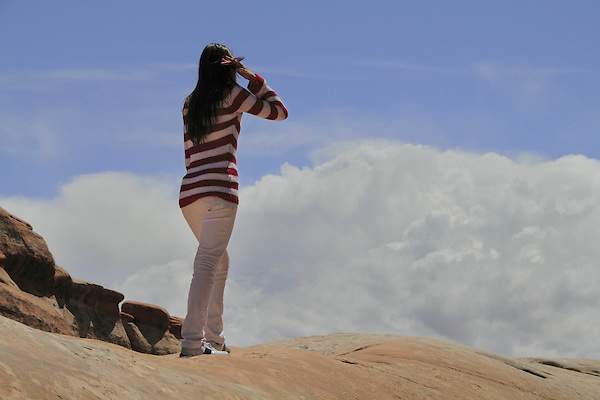 Young Hispanic woman enjoying the view in Arches National Park, Utah, USA. .  John offers private photo tours in Arches National Park and throughout Utah and Colorado. Year-round.