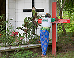 Antonia Silva Lima, a farmer in the Brazilian Amazon where Norte Dame de Namur Sister Dorothy Stang worked, prays beside the grave of the U.S. nun in Anapu, Brazil. Stang was assassinated in 2005. The red cross bears the names of 16 local rights activists who have been murdered since Stang's killing. Church activists say the killings continue, and they're about to erect a second red cross with even more names.