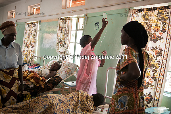 Nurse attaches IV fluid to the hook on the wall in the postnatal ward of maternity ward of Arua Hospital, Uganda.