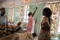 Nurse attaches IV fluid to the hook on the wall in the postnatal ward of maternity ward of Arua Hospital, Uganda.
