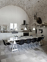 The kitchen/dining area is a contrast of styles, with vintage Eames chairs surrounding a simple trestle worktable, matched with a contemporary 'country style' kitchen