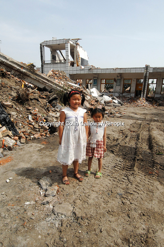 Students Fu Ting, 6, and Pou Shuting, 8, stand in the rubble of Long Qu primary school, where 60 students died in the earthquake..18 May 2008
