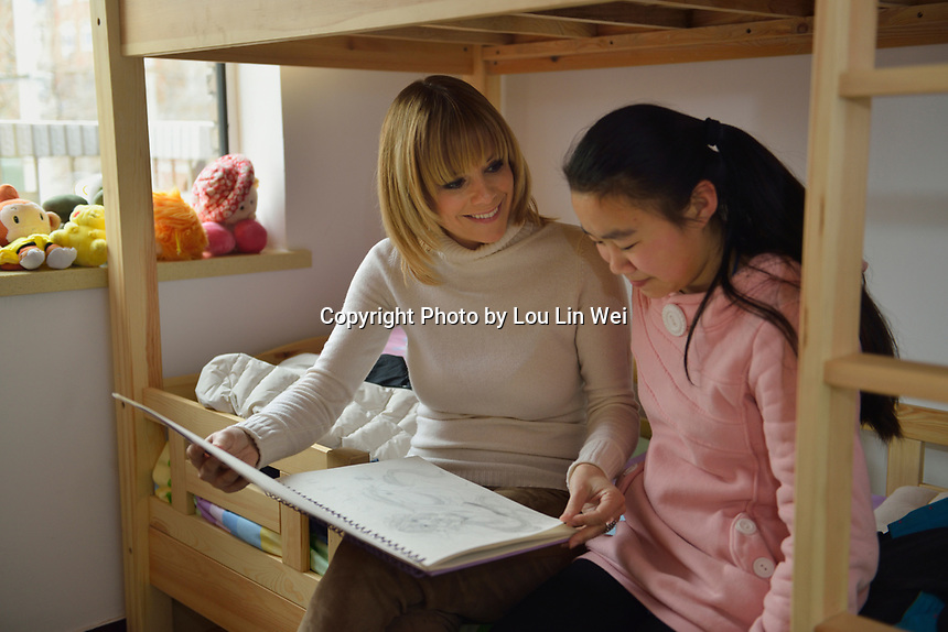"Swiss singer and TV presenter Francine Jordi views paintings by Qu Yuanyuan in her room while visiting ""SOS Kinderdorf"" in Tianjin, China.  22-Mar-2016"