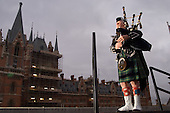 Willie Cochrane pipes in the dawn on the roof of Camden Town Hall overlooking St Pancras on the day the station opens for Eurostar passengers.