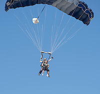 NWA Democrat-Gazette/J.T. WAMPLER Julie Zimmerly of Bentonville floats to the ground Sunday Aug. 9, 2015 during a tandem parachute jump with Brad Barnett of Springfield at the Skydive Skyranch in Siloam Springs. Zimmerly  was one of around forty people who raised at least $1,000 each for the SkyDive for Kids fundraiser for the Children's Advocacy Center of Benton County. The CAC provides a safe place for child abuse victims and their families to receive comprehensive services from dedicated professional interviewers, nurses, counselors and advocates.