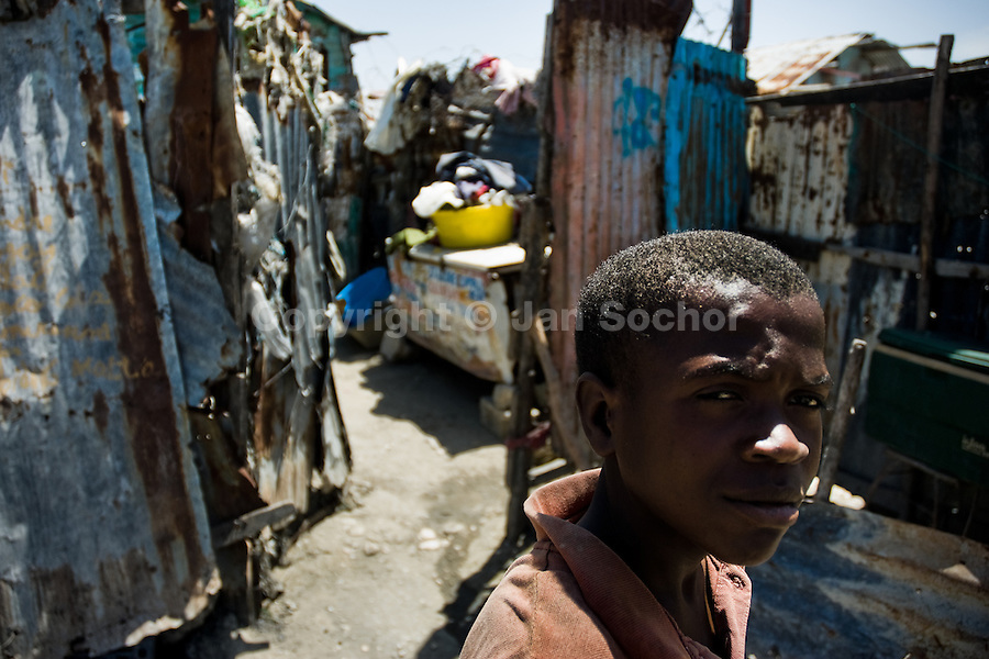 A Haitian boy walks in front of a shack in the slum of Cité Soleil, Port-au-Prince, Haiti, 11 July 2008. Cité Soleil is considered one of the worst slums in the Americas, most of its 300.000 residents live in extreme poverty. Children and single mothers predominate in the population. Social and living conditions in the slum are a human tragedy. There is no running water, no sewers and no electricity. Public services virtually do not exist - there are no stores, no hospitals or schools, no urban infrastructure. In spite of this fact, a rent must be payed even in all shacks made from rusty metal sheets. Infectious diseases are widely spread as garbage disposal does not exist in Cité Soleil. Violence is common, armed gangs operate throughout the slum.
