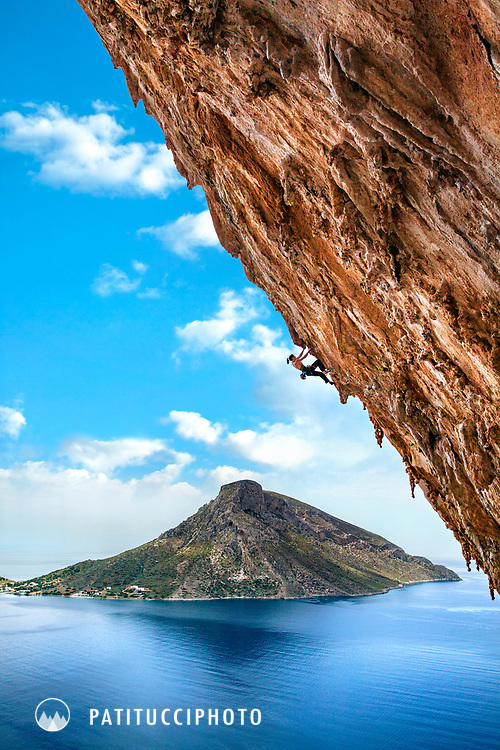 A female sport climber climbing in the incredibly steep Grande Grotta cave above the Aegean Sea on the island of Kalymnos, Greece
