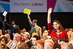 © Joel Goodman - 07973 332324 . 23/09/2013 . Brighton , UK . Members of the audience raise their hands in a bid to speak from the stage during the Britain's Global Role session . Day 2 of the Labour Party 's annual conference in Brighton . Photo credit : Joel Goodman