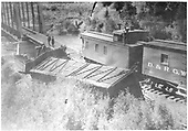 Derailed stock car and gondola at bridge. Standard gauge caboose 0876 on track.<br /> D&amp;RGW