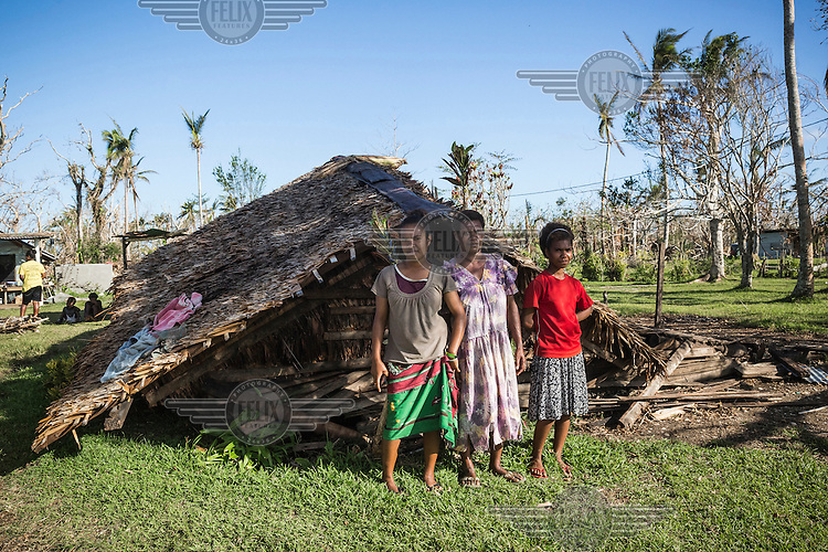 Total Sam (45) with her daughters Melina (19, left) and Sarina (14, right) outside their house, which was badly damaged by Cyclone Pam on 13 March 2015. She says: 'Our house wasn't strong enough to hold the strong wind. We still use the house, but it's very dangerous to sleep here, so we come here to cook only and we sleep outside.'
