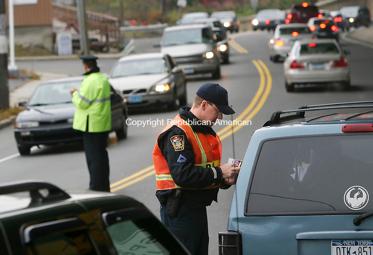 SEYMOUR, CT 11/21/07- 112107BZ04- Seymour Police Officer Thomas Scharf cites a driver for failing to wear a setabelt as Ansonia Police Officer Jim Frolish looks for violators during a seatbelt check on Route 67 in Seymour Wednesday afternoon.  Officers from Ansonia, Derby, Shelton and Seymour were at the site as part of the Click It or Ticket campaign.<br /> Jamison C. Bazinet Republican-American