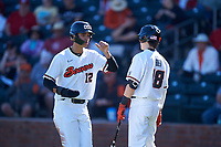 Oregon State Beavers Micah McDowell (12) is congratulated by Ryan Ober (18) after scoring a run during an NCAA game against the New Mexico Lobos at Surprise Stadium on February 14, 2020 in Surprise, Arizona. (Zachary Lucy / Four Seam Images)