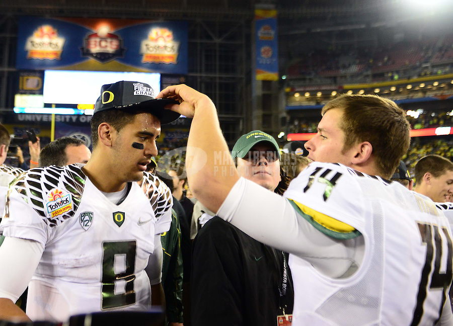 Jan. 3, 2013; Glendale, AZ, USA: Oregon Ducks quarterback Marcus Mariota (8) gets a Fiesta Bowl champions hat from Dustin Haines (14) following the game against the Kansas State Wildcats during the 2013 Fiesta Bowl at University of Phoenix Stadium. Oregon defeated Kansas State 35-17. Mandatory Credit: Mark J. Rebilas-