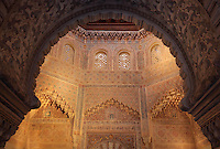 Oratory or Sala de la Oracion seen through a carved horseshoe arch, with the mihrab below, in the Madrasa of Granada, a mosque school founded 1349 by the Nasrid King Yusuf I, Sultan of Granada, in El Albayzin, the medieval Moorish old town of Granada, Andalusia, Southern Spain. The madrasa functioned as a university until 1499 and is now part of the University of Granada. From the 8th to the 15th centuries, Granada was under muslim rule and retains a distinctive Moorish heritage. Granada was listed as a UNESCO World Heritage Site in 1984. Picture by Manuel Cohen