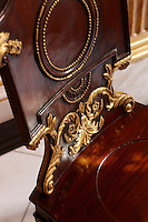 A detail of a wooden chair with gold ormolu decoration.